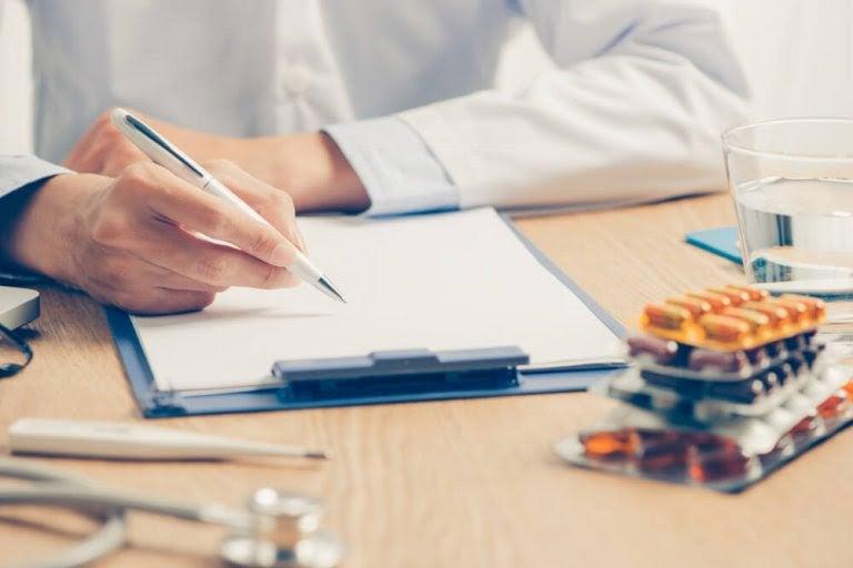 läkare med skrivblock och läkemedel