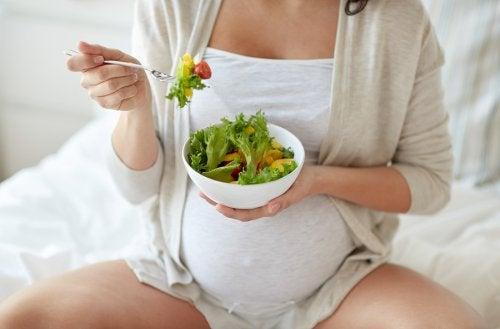 En gravid kvinna äter sallad.