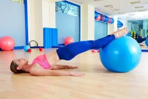 En kvinna tränar med hjälp av en pilatesboll.