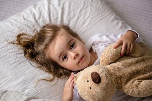 Klarvaken flicka i säng med nalle