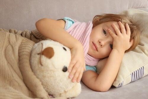 Barn med epilepsi: Orsaker, symtom och behandling: flicka i säng med nalle