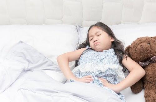 Barn med epilepsi: Orsaker, symtom och behandling: flicka i säng ser plågad ut och håller sig för magen