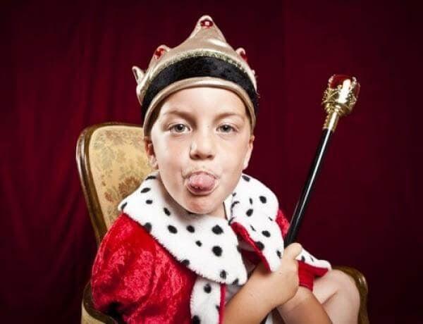 pojke i kungakläder räcker ut tungan