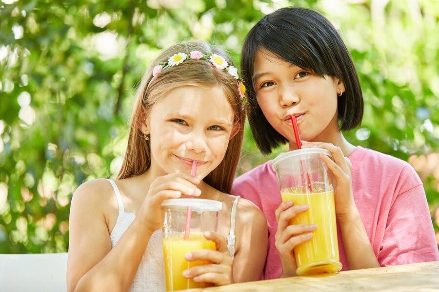 Två flickor dricker juice