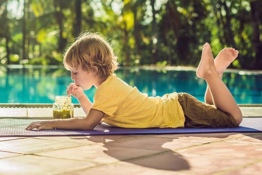 barn ligger på marken framför en pool och dricker grön juice