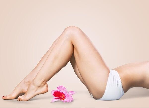 Kvinnors biologiska klocka: underkropp på liggande kvinna som svankar, rosa blommor på golvet