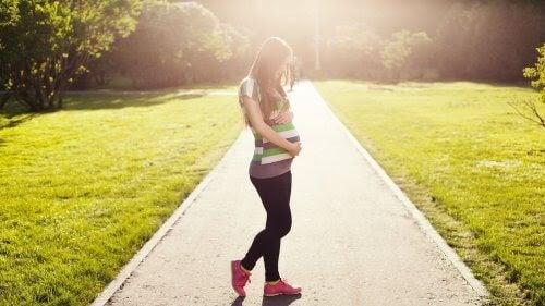 gravid kvinna på promenad i motljus
