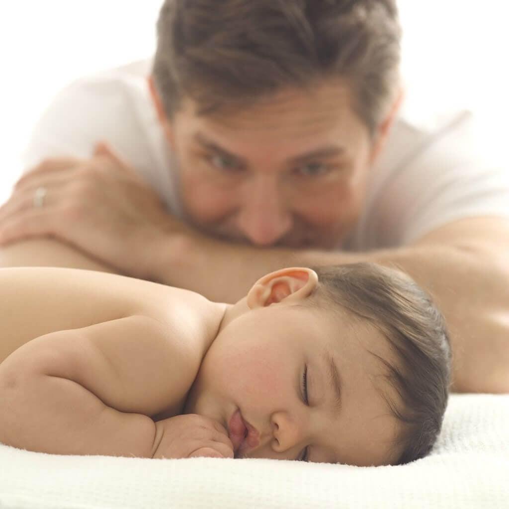 man tittar på sovande spädbarn