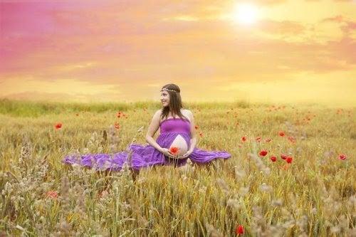 Gravid kvinna i ett soligt fält med blommor
