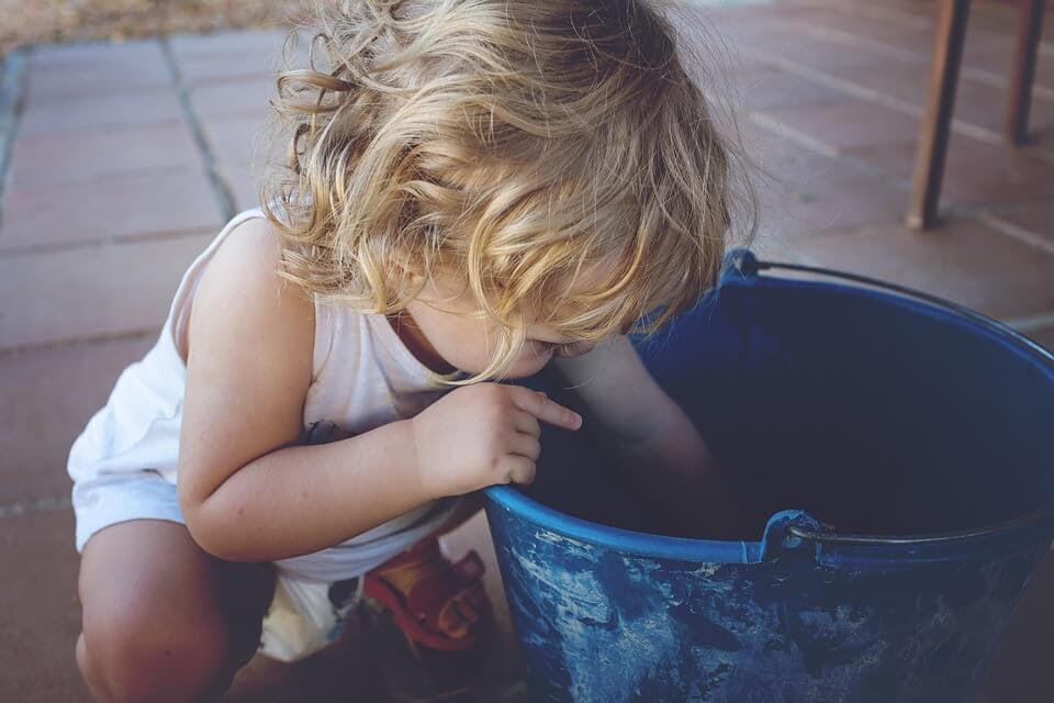 Litet barn leker med spann