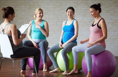 fyra gravida kvinnor på pilatesbollar