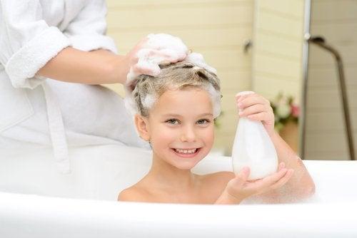 Ett barn i badet får sitt hår tvättat.
