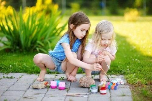 Två flickor målar på stenar.