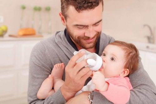 En pappa matar sin bebis med nappflaska.