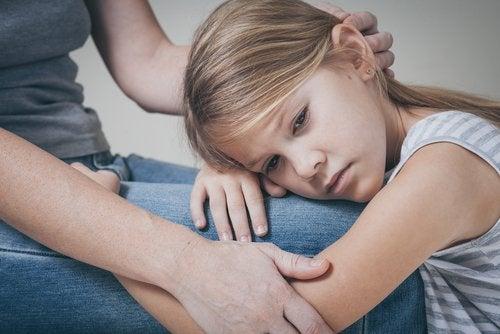 Flicka som ligger i sin mammas knä.