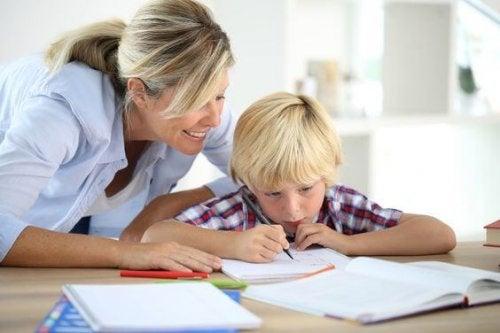 En mamma hjälper sin son med läxorna.