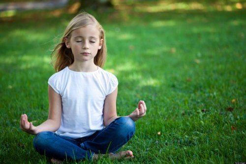 En flicka mediterar i en park.