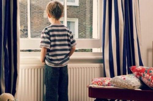 Pojke som står vid fönster.