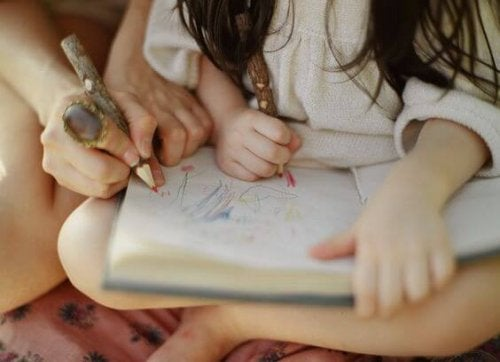 Ett barn ritar tillsammans med en vuxen.