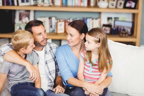 Man, kvinna och två barn sitter i soffa