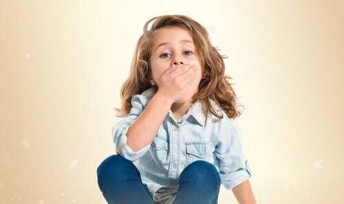 Barn håller sig för munnen