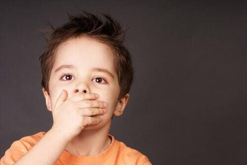 Pojke med handen för munnen