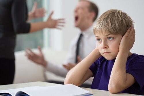 Pojke håller för öronen medan föräldrarna bråkar i bakgrunden