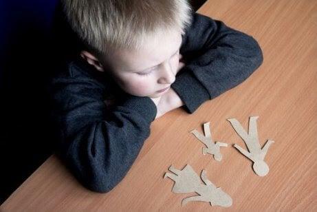 Pojke tittar på pappersdockor av mamma, pappa och barn