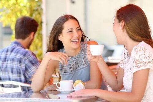 Kvinnor skrattar och dricker kaffe