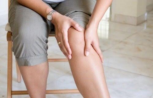 kvinna håller om sitt knä