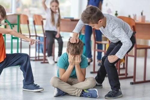 pojke sitter på golvet med händerna för ansiktet, andra barn slår och pekar på honom