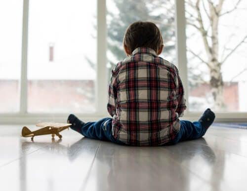 Pojke sitter på golvet med ryggen mot kameran