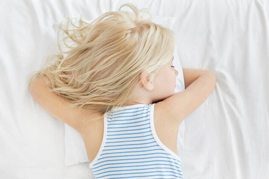 Flicka sover på mage