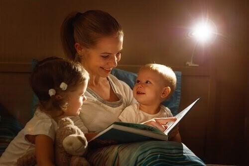 mamma läser godnattsaga för två små barn
