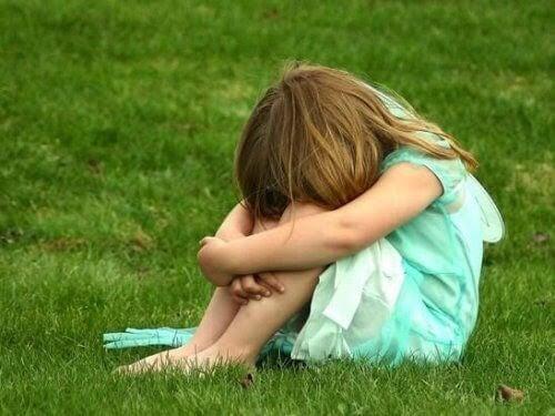 Flicka sitter ihopkrupen på gräs