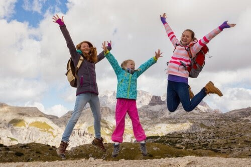 Tre flickor hoppar mot bakgrund av berg