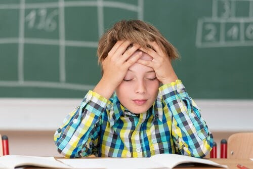 pojke vid skolbänk håller sig för huvudet