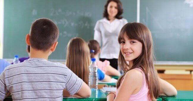 Flicka tittar in i kameran i klassrum
