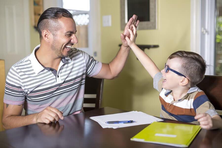 Man och pojke gör high five över läxor