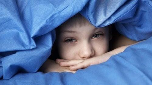 sömnigt barn tittar fram ur täcke
