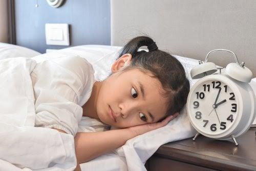 flicka i säng bredvid väckarklocka