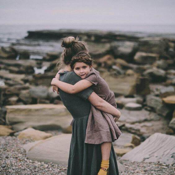 Mamma håller dotter på strand