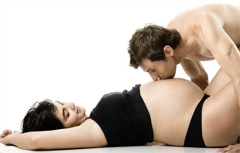 man kysser gravid kvinnas mage
