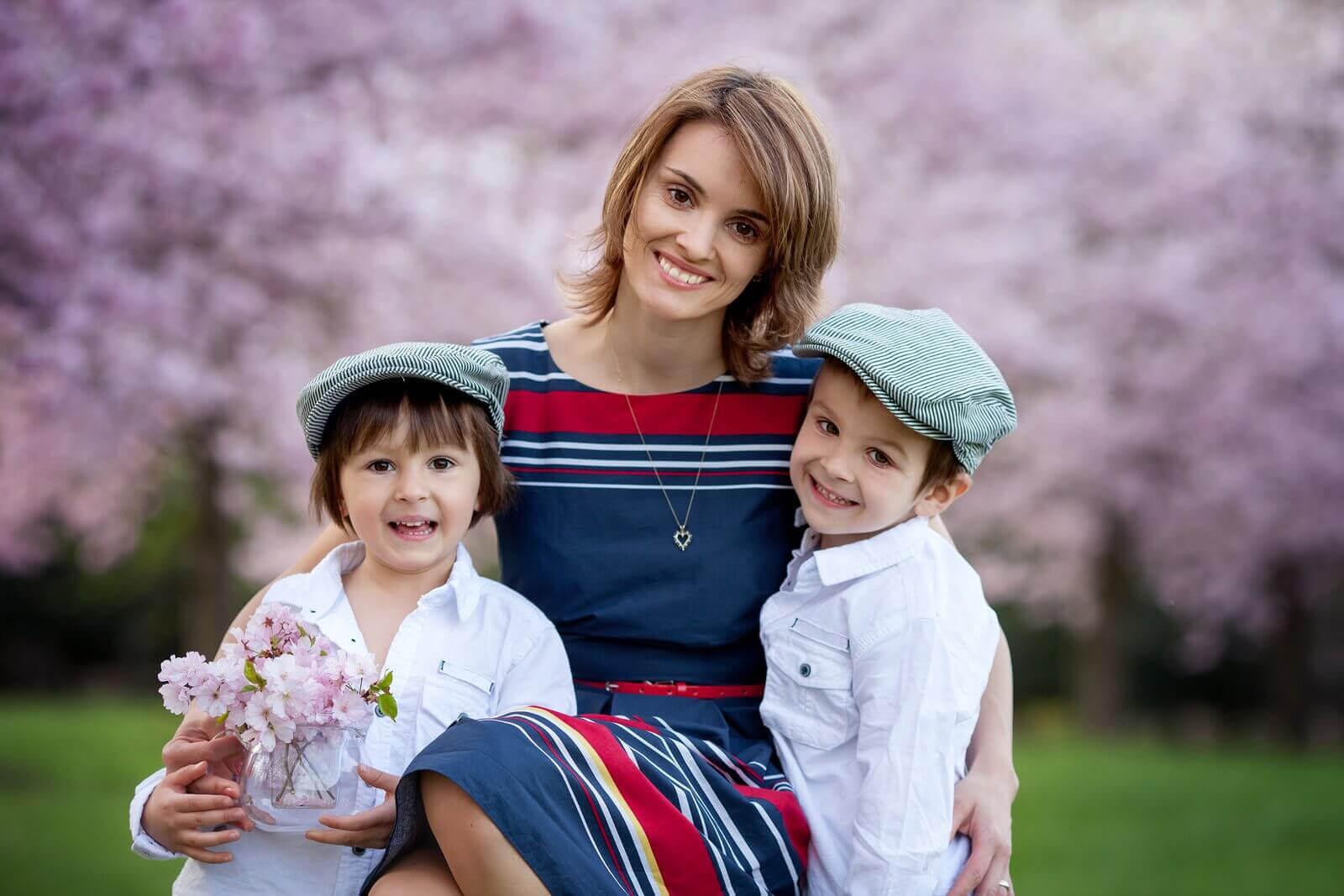 Mamma håller två barn