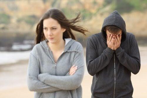 ungt par på strand, ser ut att vara ovänner