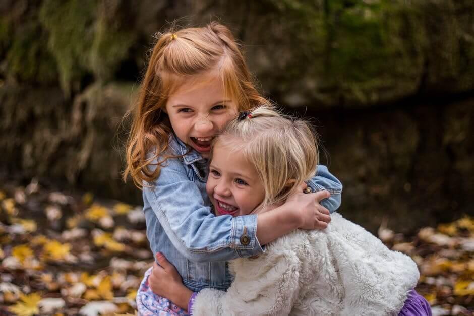 två tjejer kramar varandra