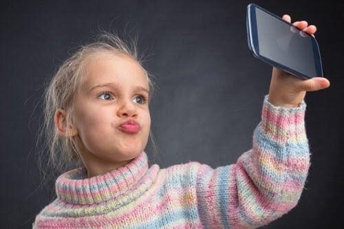 barn håller mobiltelefon tar selfie