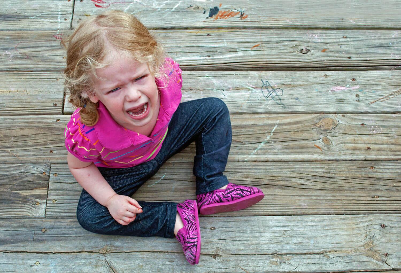 Sittande flicka skriker och gråter