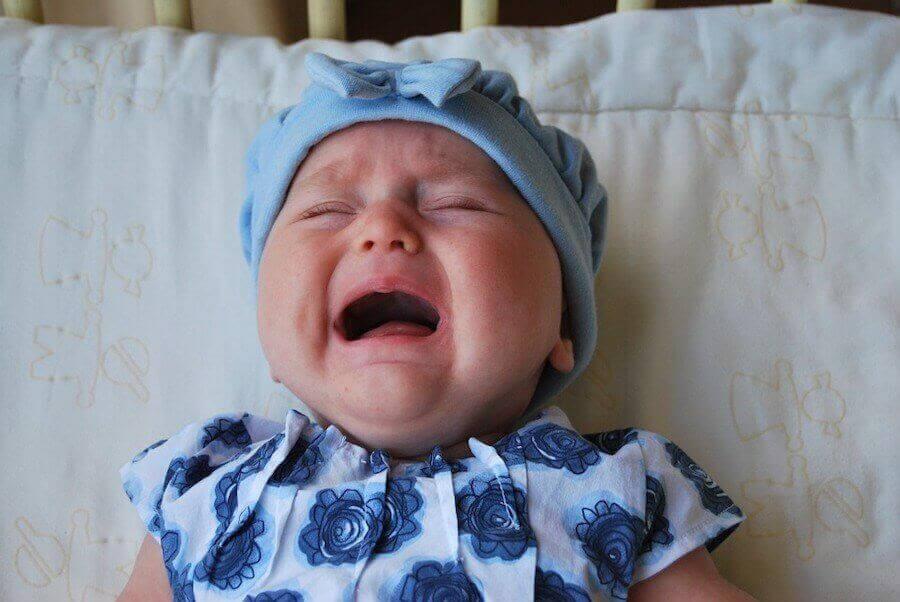 gråtande bebis i blå mössa