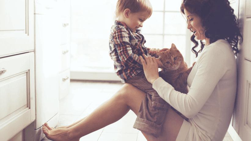 Mamma håller son och katt